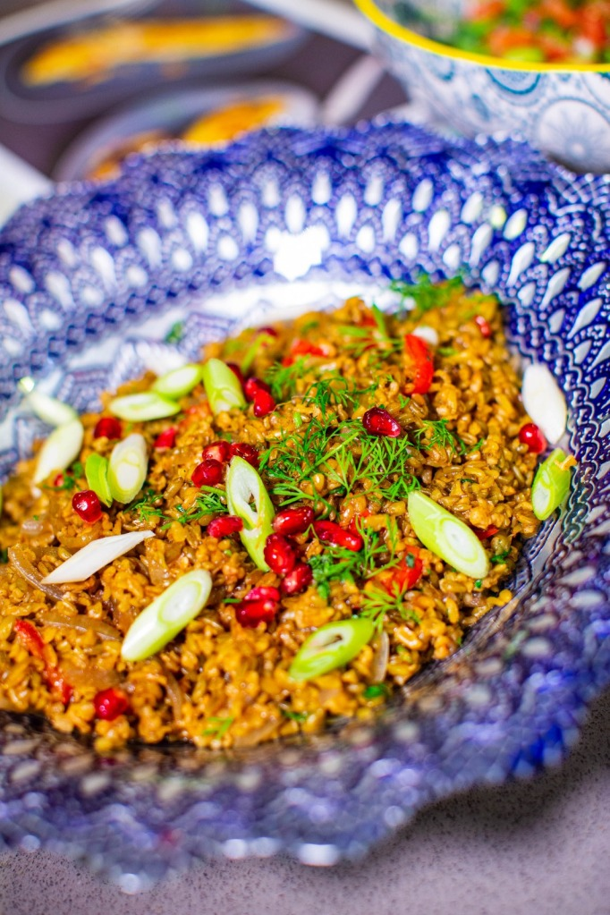 freekeh pilaf with pomegranate in blue bowl
